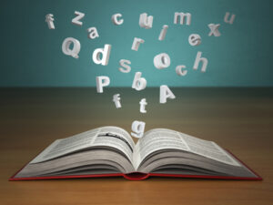 Open book with falling letters on green vintage background. Create a Winning Culture with One Key Word!