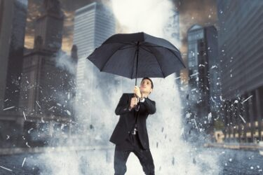Safety Comes First! Businessman protected with umbrella from ice flow