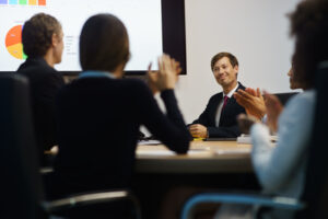Business People Applauding Manager Doing Presentation In Meeting