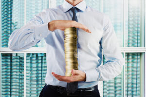 Businessman holds in his hands a stack of coins